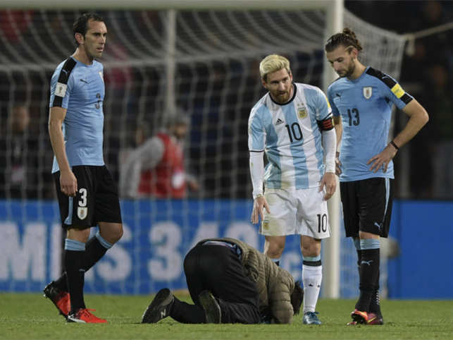A fan kisses Lionel Messi's feet during a match.