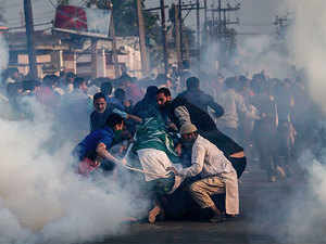 Relatives and neighbors huddle around the body of 12-year-old Junaid as tear gas shells fired by security forces explode near them during his funeral procession in Srinagar on October 8.