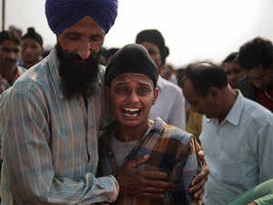 Brother of Indian woman Rajinder Kaur, who was killed in Pakistani shelling wails during her funeral at Khour village in Ramgarh sector, Samba district of Jammu and Kashmir, India, on Tuesday.