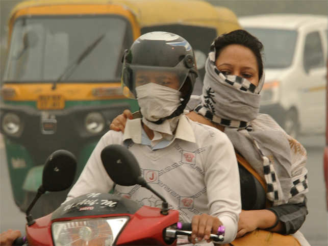 Commuters use handkerchiefs and scarves as protection against air pollution due to the heavy smog in Delhi.