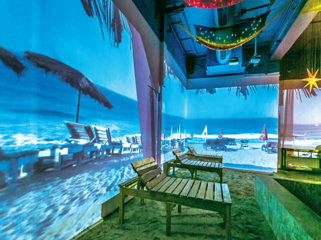 A wall-to-wall video projection of beach and beach beds at Lady Baga.