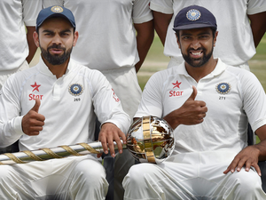 Virat Kohli and teammate R Ashwin pose with the trophy after winning the Test series against Australia at HPCA Stadium in Dharamsala.