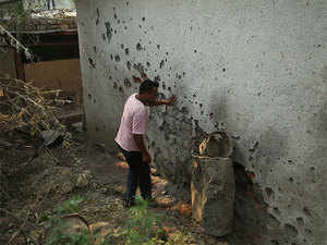 A civilian looks at a wall with marks of mortar shells fired allegedly from the Pakistan side of the border, at a residential area near the Line of Control on the India Pakistan border at Jhanghar village, in Nowshera, India, Sunday, May 14,2017.