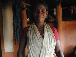 A tribal woman in Kandhamal's Burlubaru village showing millets she has grown in her forest farm