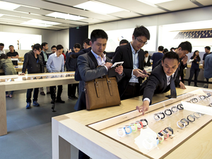 Customers look at Apple Watches.