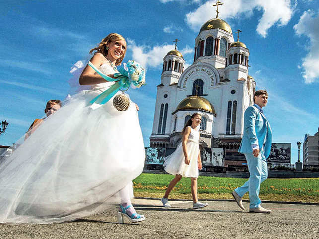 A newly wed couple walks happily in front of The Savior on Blood Cathedral in Yekaterinburg, Russia