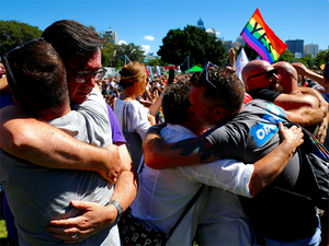 People celebrate after it was announced the majority of Australians support same-sex marriage in a national survey, at a rally in Sydney