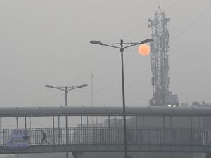 A school boy walks across a pedestrian bridge as the morning sun is enveloped by a blanket of smog in New Delhi.