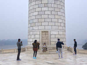 Tourists take photo against one of the freshly cleaned up minarets of the Taj Mahal.