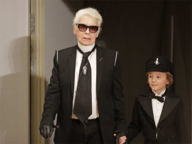Fashion designer Karl Lagerfeld and a boy walk over the stage at Chanel's pre-fall Metiers d'Art fashion show in the new Elbphilharmonie concert house in Hamburg, northern Germany.