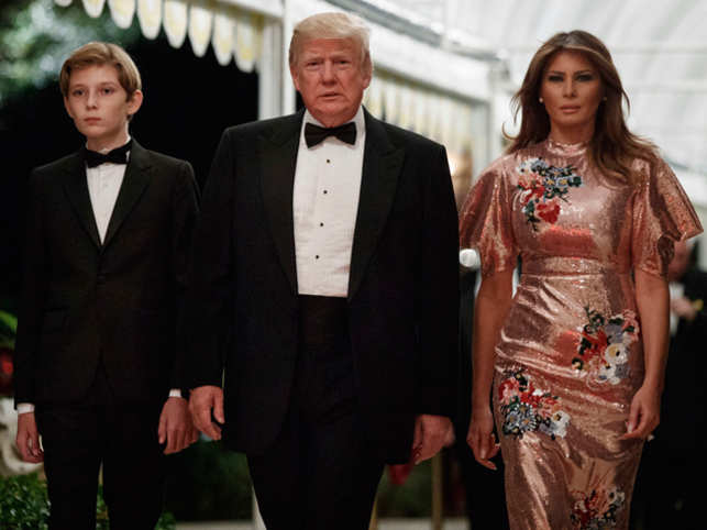 President Donald Trump arrives for a New Year's Eve gala at his Mar-a-Lago resort with first lady Melania Trump and their son Barron, Sunday, Dec. 31, 2017, in Palm Beach, Fla.