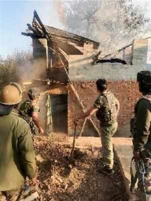 Srinagar: Security forces personnel dousing the fire at a slain PDP leader's hou...