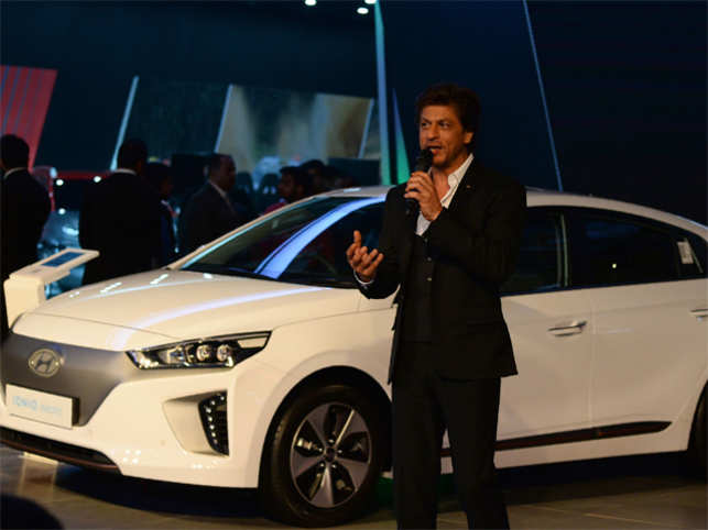 Shah Rukh Khan speaks near the Hyundai's Ioniq electric car before the launching of 'Swachh Can', a portable bin for new Hyundai cars -- part of its efforts to support India's nationwide cleanliness drive known as 'Swachh Bharat Abhiyan' -- during the Indian Auto Expo 2018.