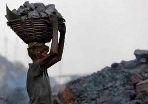 Dhanbad: A labourer carries coal on his head at Jharria and Digwadih area in Dha...