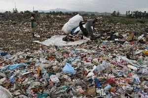 Jammu: A rag picker sift through a garbage dump in search of recyclables on the ...
