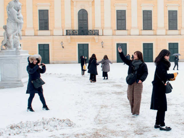 Tourists take selfies as they stand on the snow-covered esplanade in front of the Schoenbrunn Castle in Vienna, Austria.