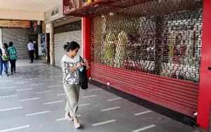 New Delhi: A woman walks past a closed shop during a strike by traders and worke...