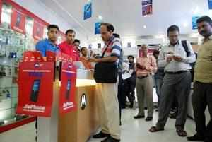 New Delhi: People filling forms to buy JIO mobile phones in New Delhi on Thursda...