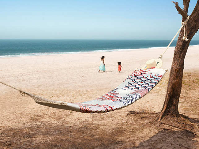 Trade the usual netted hammock for one made from your favourite old bedsheet.
