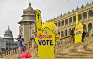 Bengaluru: Workers put promotional posters for the forthcoming Karnataka Assembl...