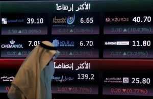 FILE PHOTO: An investor walks past a screen displaying stock information at the Saudi Stock Exchange (Tadawul) in Riyadh, Saudi Arabia