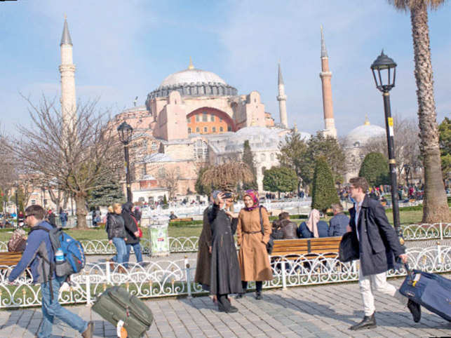 Tourists walk past the Hagia Sofia in the famous Sultanahmet District in Istanbul, Turkey