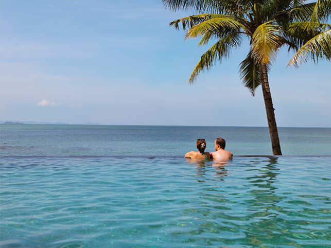 travel-couple-honeymoon-pool-sea-ThinkstockPhotos-545118228