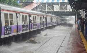 Mumbai: A train chugs at water-logged tracks during heavy rains in Mumbai on Sat...