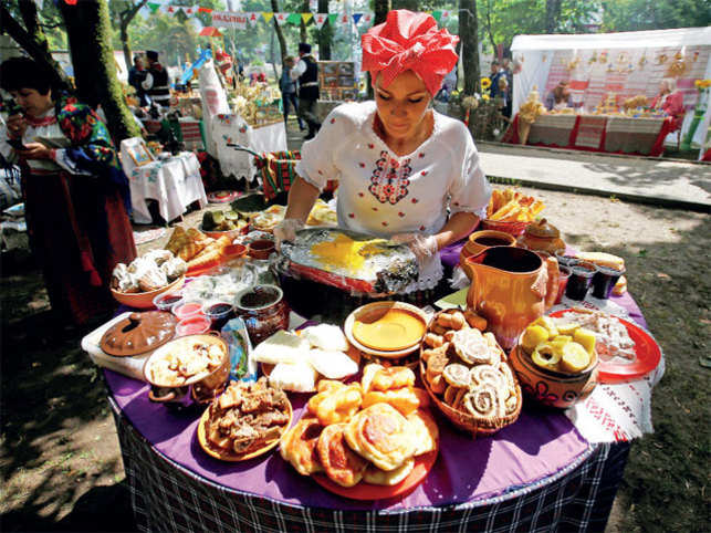 A woman dressed in national Belarussian clothes prepares food as she takes part in the 'Beraginya' festival of folklore art in the town of Oktyabrski