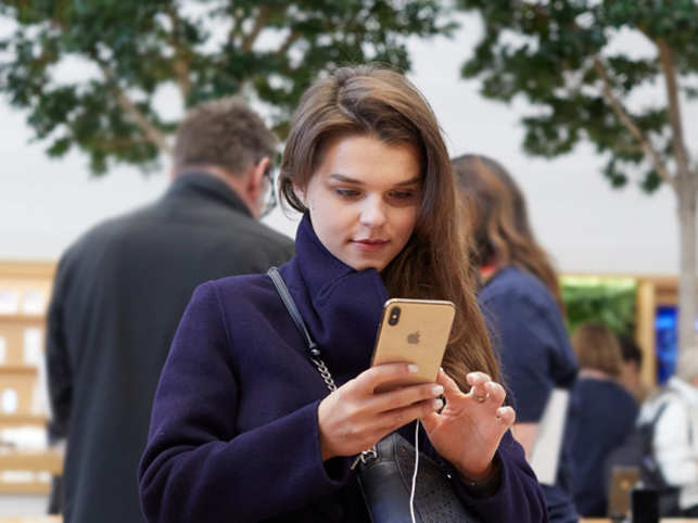 iPhone-Xs-Apple-Watch-Series-4_Regent-St-London-woman-holding-iPhone-Xs-gold_09202018