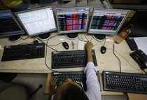A broker monitors share prices while trading at a brokerage firm in Mumbai