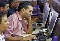 Brokers trade at computer terminals at stock brokerage firm in Mumbai