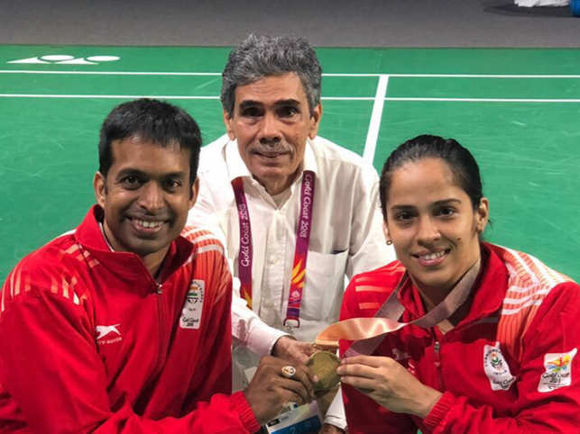 Saina Nehwal (R) with coach Pullela Gopichand (L) and father Harvir Singh Nehwal (C) after willing a gold in 2018 Commonwealth Games.