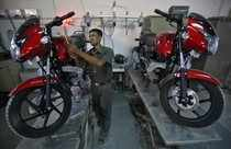 Worker prepares a Bajaj motorcycle before