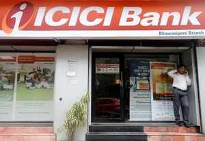 A man speaks on the phone outside an ICICI Bank branch in Kolkata