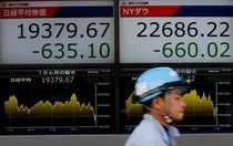 FILE PHOTO: A man walks past electronic boards showing Nikkei average (L) and the Dow Jones Industrial Average outside a brokerage in Tokyo