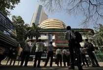 People look at a screen displaying the Sensex results on the facade of the Bombay Stock Exchange (BSE) building in Mumbai