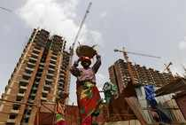 Labourers work at the construction site of a residential complex in Noida