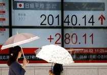 FILE PHOTO: Women holding parasols, look at an electronic board showing Japan's Nikkei average outside a brokerage in Tokyo