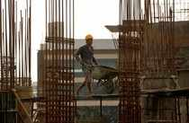 A worker pushes a wheelbarrow to collect cement at a construction site of a residential building in Mumbai