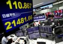 Employees of a foreign exchange trading company work next to monitors displaying Japan's Nikkei stock average and the Japanese yen's exchange rate against the U.S. dollar as a television screen broadcasting second North Korea-U.S. summit in Tokyo