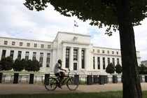 A cyclist passes the Federal Reserve building in Washington, DC
