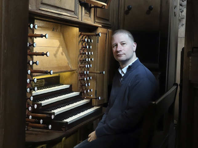 Johann Vexo, the organist who was playing at evening mass inside Notre Dame when flames began licking at the iconic cathedral's roof, poses at the pipe organ at Notre Dame de Nancy cathedral, eastern France.