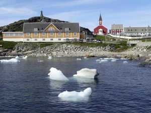 small pieces of ice float in the water off the shore in Nuuk Greenland