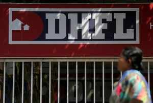 FILE PHOTO: A woman walks past a signboard of Dewan Housing Finance Corporation Ltd. (DHFL) outside its office on the outskirts of Mumbai
