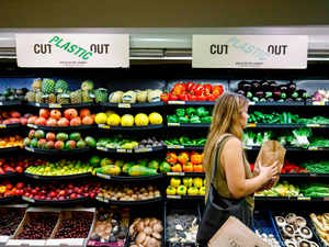 A sign promoting plastic free packaging is seen above a display of loose fresh fruit as a shopper browses at Budgens supermarket AFP
