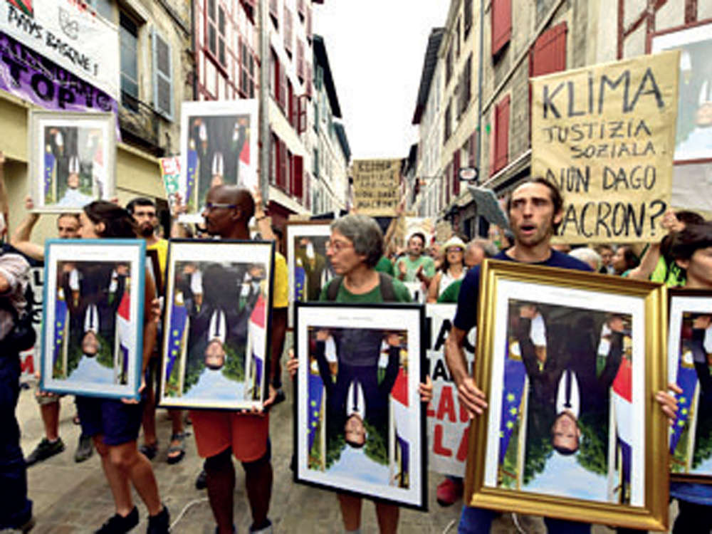 Anti-G7 protesters rally carrying 'stolen' portraits of French President
