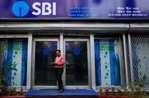 FILE PHOTO: A man checks his mobile phone in front of SBI branch in Kolkata