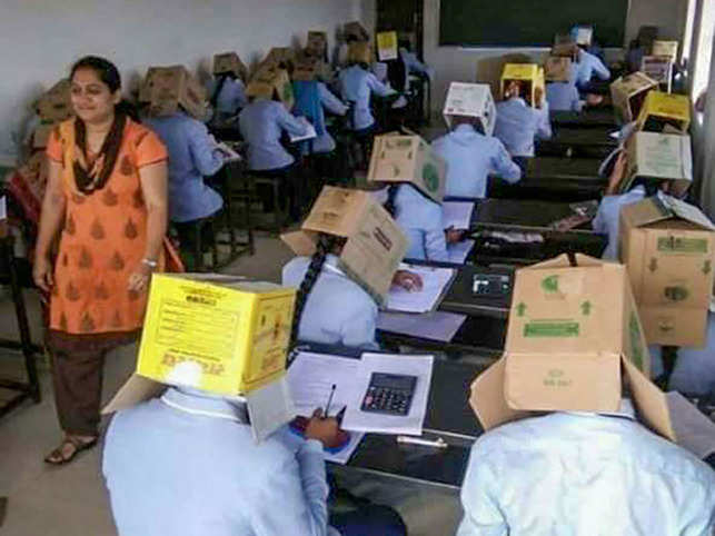 First-year science students of Bhagat PU College sit for a midterm exam with cardboard cartons covering their heads — with a hole cut out in the front for their face, in Haveri district of Karnataka.