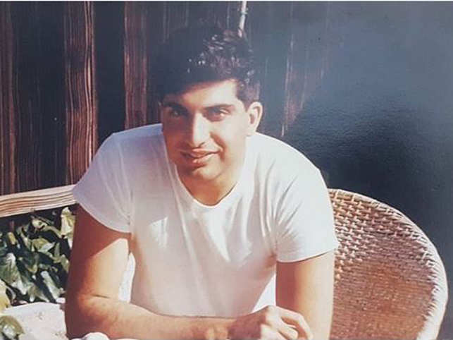 The photo shows a young Ratan Tata, clad in a white shirt, looking at the camera.